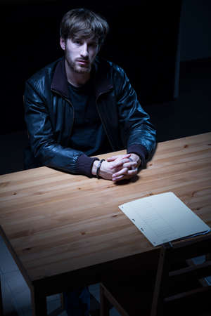 suspected: Image of young criminal sitting at police desk Stock Photo