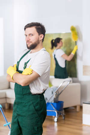 tidiness: Handsome and confident cleaner in uniform, during work