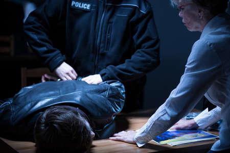 Foto van politieagent arresterende verdachte na verhoor op het politiebureau Stockfoto