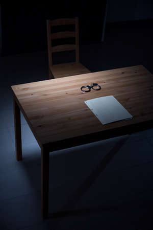 Image of empty desk with handcuffs in interrogation room Stock Photo