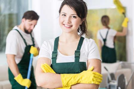 Szczęśliwa młoda sprzątaczka stoi w mundurze czyszczenia