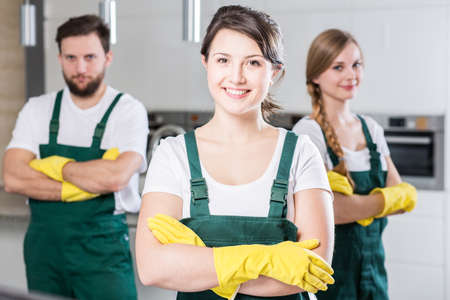 cleaning team: Professional cleaning team in uniforms and yellow rubber gloves Stock Photo