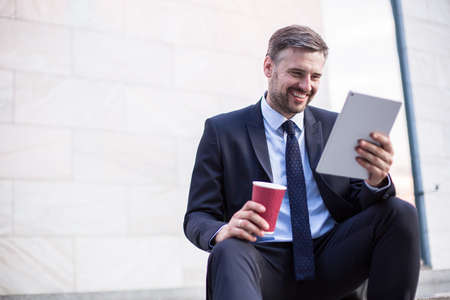 workday: Photo of smiling businessman relaxing after successful workday Stock Photo