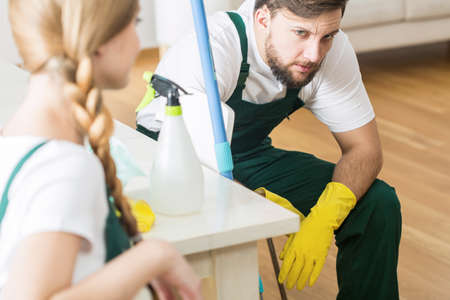 tidiness: Tired cleaner in uniform and yellow rubber gloves sitting Stock Photo