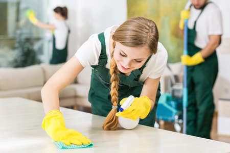 Sorridente donna delle pulizie in guanti di gomma gialli durante il lavoro