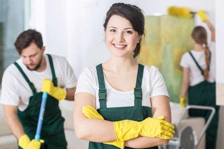 Lachende schoonmaakster in uniform en gele rubber handschoenen Stockfoto