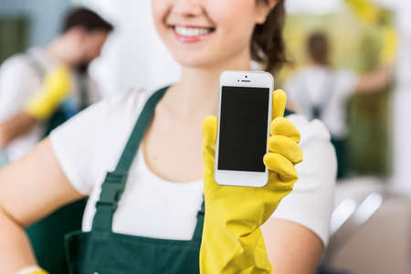 Smiling charwoman in uniform holding cellphone