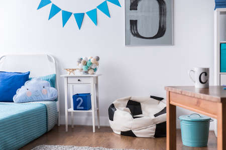 boy bedroom: Stylish boy room with bed, table and football design sack chair