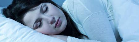 durmiendo: Panorama de la mujer joven para dormir después de duro día de invierno