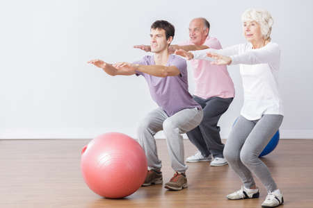 squats: Seniors doing squats during classes with physiotherapist