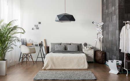 白とグレーの居心地の良いベッドルームを間します。