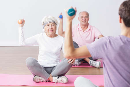 Active seniors lifting the dumbbells during fitness classes