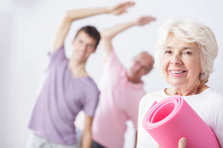 color therapist: Aged happy woman with mat ready for fitness classes