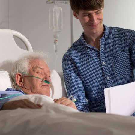 hospice: Photo of grandson visiting grandpa in hospice