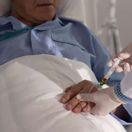 seniors suffering painful illness: Doctor performing a medical procedure on senior patient Stock Photo