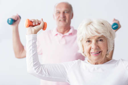 strength: Elderly active couple strengthening the muscles on gym