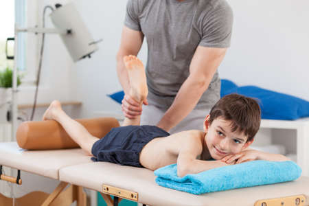 massage enfant: Garçon couché sur la table de physiothérapie et ayant un massage des jambes