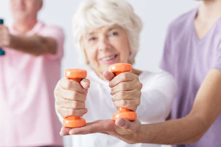 color therapist: Close-up of older woman holding two dumbbells