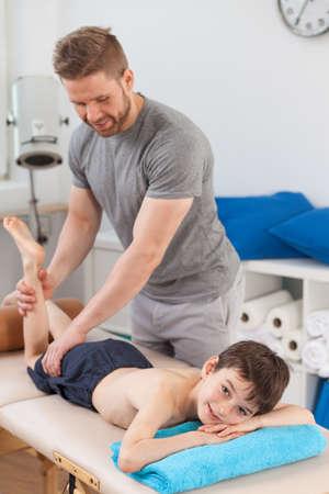 massage enfant: Homme physiothérapeute travaillant avec un garçon avec une blessure au genou Banque d'images