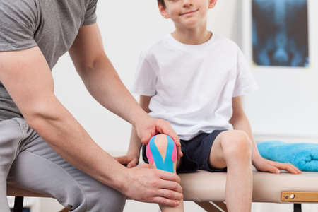 contusion: Kinesiology tape on the little boys knee Stock Photo
