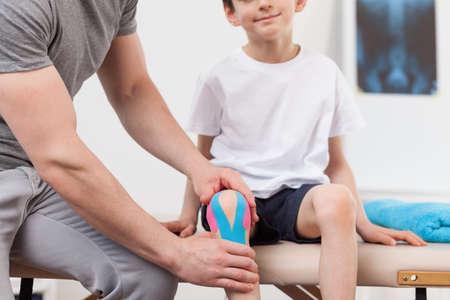 sprained joint: Kinesiology tape on the little boys knee Stock Photo