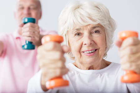 Ältere fit Frau, die Aufhebung zwei Hanteln Standard-Bild