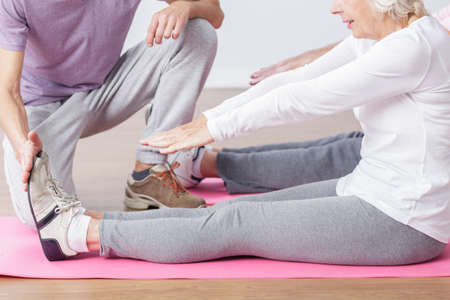 color therapist: Older active woman stretching her legs on gym