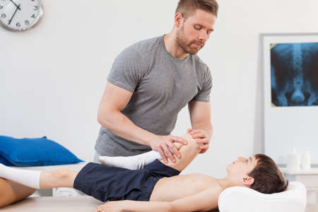 sprained joint: Little patient after sports injury visiting a physiotherapist Stock Photo