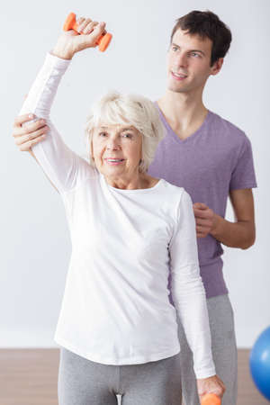 Helpful young physical therapist and older exercising woman Stock Photo