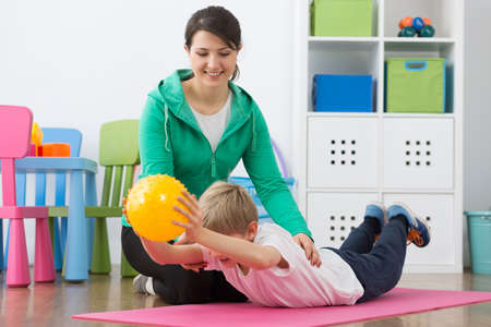 gym ball: Boy exercising with small gym ball and his smiling instructor Stock Photo