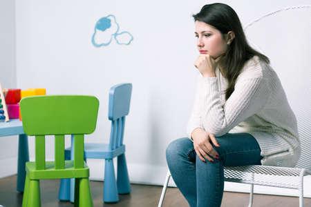 bebe sentado: Mujer triste que se sienta en la habitaci�n del beb�, falta a su hijo