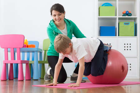 Boy exercising with instructor on gym ball