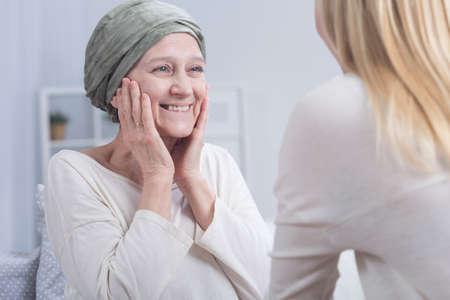 Sonriente mujer de cáncer con pañuelo en la cabeza y la muchacha rubia joven