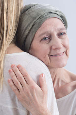 inner strength: Positive cancer woman with headscarf embracing young girl Stock Photo
