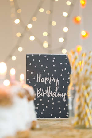 birthday decoration: Black birthday card  and cream puffs lying on gold decorated table Stock Photo