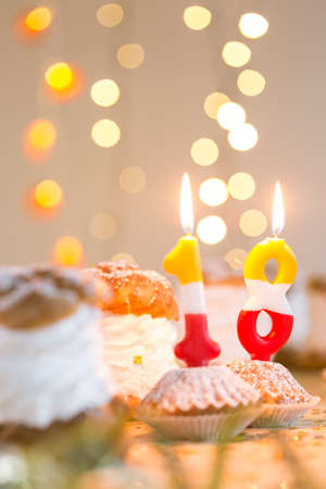 party pastries: Number eighteen birthday candle, cream puffs and cupcakes lying on table