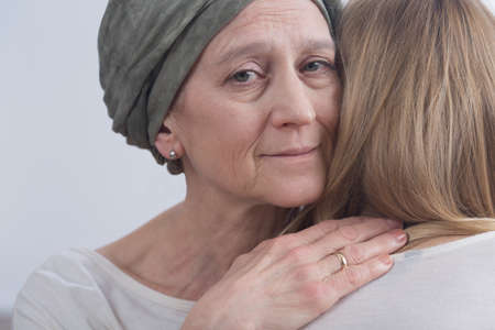 inner strength: Cancer woman with headscarf embracing young girl Stock Photo