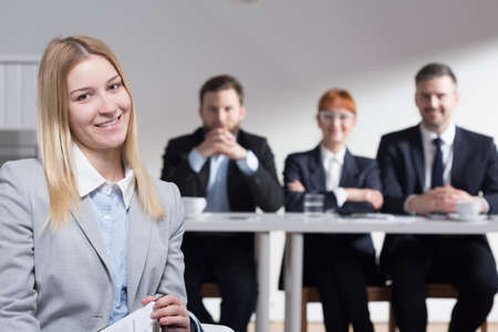 beside table: Happy elegant woman after successful job interview, and three businesspeople sitting beside table