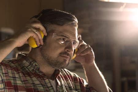 Knappe timmerman in hoofdtelefoons en veiligheidsbril