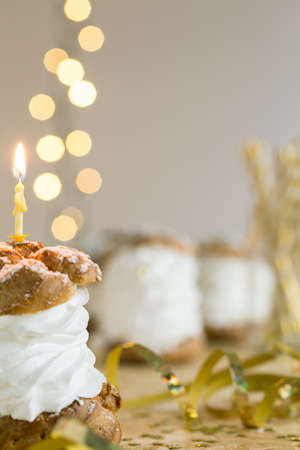 cream puff: Cream puff with birthday candle lying on golden decorated table Stock Photo