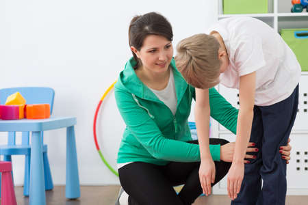 faulty: Happy woman physiotherapist and boy during exercises Stock Photo