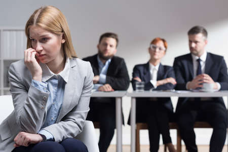 beside table: Stressed applicant and management members sitting beside table