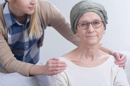 inner strength: Tired cancer woman with headscarf and young girl holding hands on her arms Stock Photo