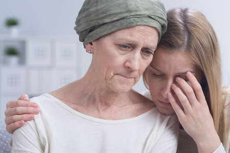 Sad woman with headscarf during chemotherapy embraced by young woman