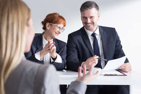 company job: Job applicant back view and two elegant corporate workers Stock Photo