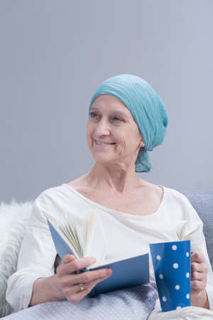 sick leave: Positive cancer woman with cancer holding book and cup, relaxing Stock Photo