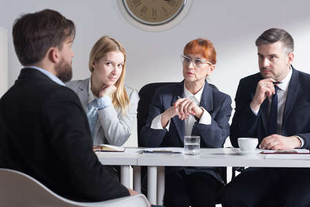 beside table: Man back view during job interview and three businesspeople sitting beside table Stock Photo