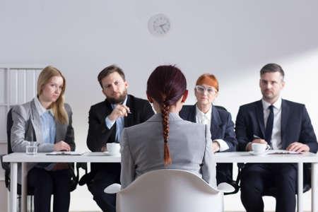 entrevista de trabajo: Mujer durante la entrevista de trabajo y cuatro miembros elegantes de gestión