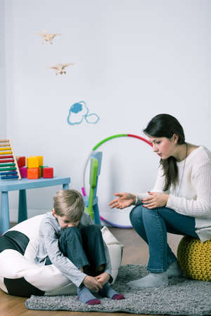 pouty: Woman reprimanding small boy, sitting in child room