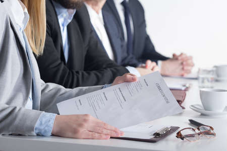 sittting: Woman holding CV sittting next to three businesspeople beside table